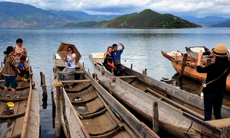 Tourists take photos beside the Lugu Lake: in 2012, 1.5 million tourists visited the region, nearly three times as many as the previous year. Photograph: Chen Haining/Xinhua Press/Corbis
